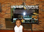 Flor, in front of one of the posters about Andy&#039;s company, &quot;Crusher Company.&quot;